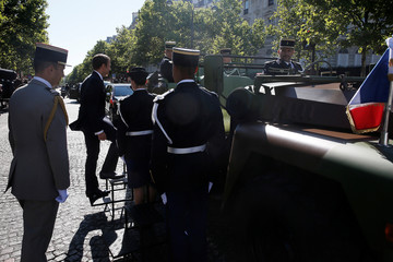 French President Emmanuel Macron climbs the steps to enter the command car as he arrives for the annual Bastille Day military parade on the Champs-Elysees in Paris