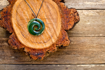 Maori New Zealand Greenstone pounamu jade Koru (spiral fern) shape pendant on cross section of timber log