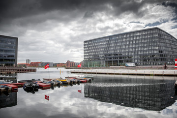 Copenhagen modern architecture on the canal bank, boats, Danish flag