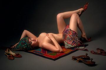 Photo sur Aluminium Akt Naked indian female in vintage beaded semi-precious stones perak cap adornment ornament lies on the carpet with many antique shoes modjari, paduka and punjabi jutti