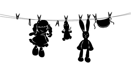 Silhouette toys drying on rope after washing