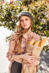 Young model stand on the street and hold bread
