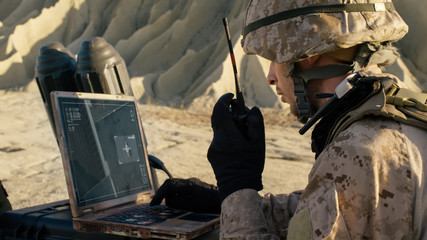 Soldier is Using Laptop Computer for Tracking the Target and Radio for Communication During Military Operation in the Desert