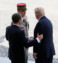 French President Emmanuel Macron and US President Donald Trump speak with French army general Bruno Le Ray, military governor of Paris, at the end of the traditional Bastille Day military parade