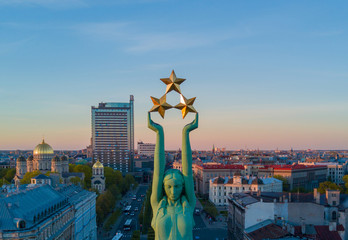 Beautiful sunset view in Riga by the statue of liberty - Milda. Freedom in Latvia. Statue of liberty holding three stars over the city. Latvian spirit. Wall mural