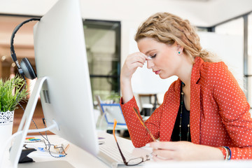 Young woman in office tired