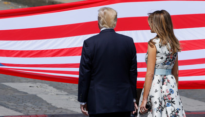 US President Donald Trump and First Lady Melania Trump stand in front of the American flag at the end of the traditional Bastille Day military parade