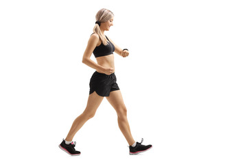 Woman walking and checking her sports watch