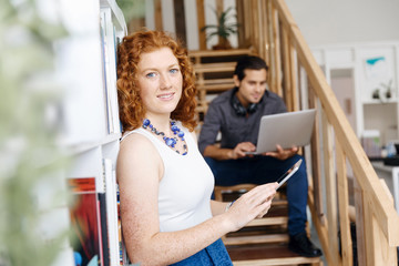 Portrait of two young people sitting at the stairs in office