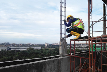 Construction workers wearing safety harness and adequate safety gear while working at high level at the construction site in Seremban, Malaysia.