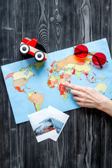 planing trip with child with pictures and map dark background top view