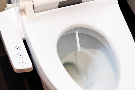 Toilet bowl with electronic control bidet. Water sprays from the toilet bowl. A cleansing jet of water designed to cleanse the anus of the user of this bidet-style toilet.