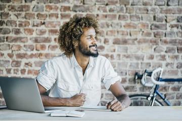 Smiling young man at desk thinking