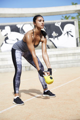 Fit woman exercising with kettlebell outdoors