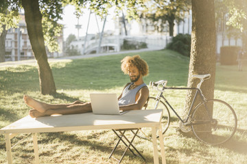 Man with beard and curly hair using laptop at table in park