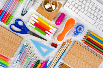 Above view of school and office supplies on wooden table