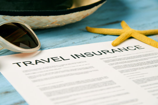 sunglasses, straw hat and travel insurance policy