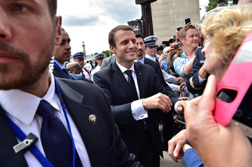 French President Emmanuel Macron greets people after attending the annual Bastille Day military parade on the Champs-Elysees in Paris