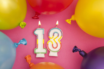 Happy Birthday number 18 celebration candle with colorful balloons