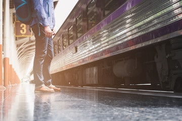 asian man with backpack standing on platform at train station. backpacker or traveler waiting for train. journey, trip, travel concept