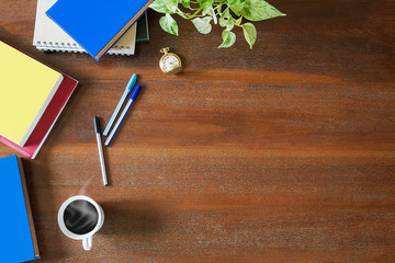 Messy textbooks, notebooks, documents,pens,green plant,pocket watch and hot white coffee cup on vintage grunge wooden background, business concept