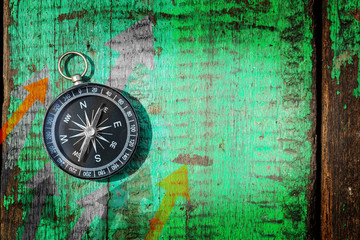 compass on old grunge wood background, flat top view, Find the better direction concept