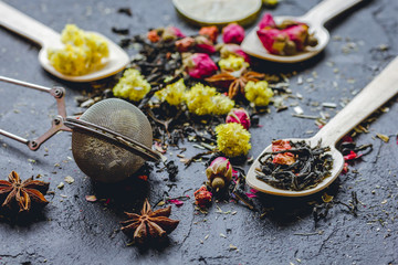 Tea herbs and spoons on grey background