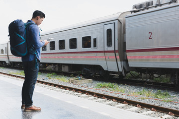 asian man with backpack standing on platform at train station. backpacker or traveler look at digital tablet while waiting for train. journey, trip, travel concept