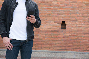 young asian man wearing black jacket and blue jeans standing near old orange brick wall with mobile smart phone
