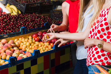 Three young women at grocery market. Women choose fruit. The middle plan. Focus on the hands.