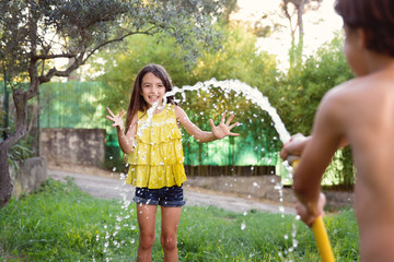 smiling girl being sprayed with hose