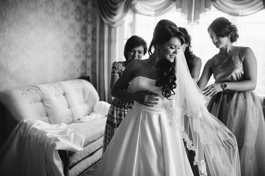 Stylish beautiful bridesmaids helping gorgeous brunette bride in white dress get ready for wedding, morning preparations, woman putting on dress