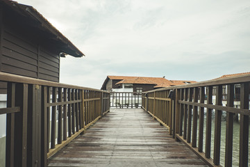 Travel holiday attraction, wooden modern design hotel on water over cloudy sky background.