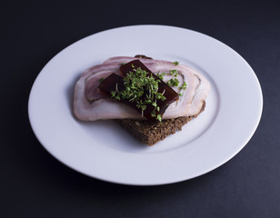 Danish open faced sandwich (smoerrebroed) with Danish cold cut made from pork (rullepoelse), aspic jelly (sky) and garden cress on dark rye bread. Placed on white plate on a black background.