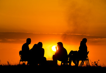 group of people in camping sitting near campfire against sunset