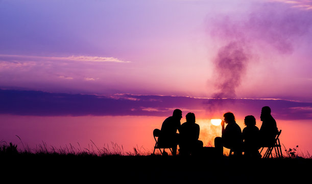 people sitting near campfire against sunset with copyspace