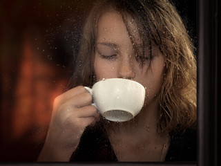 To watch through the glass as the girl drinks coffee from a Cup. The window in raindrops