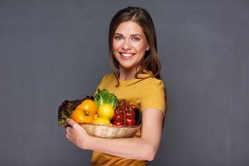 Smiling woman holding vegan food ingredients.