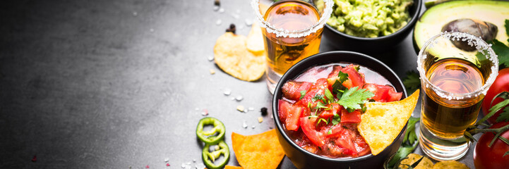 Latinamerican food party sauce guacamole, salsa, chips and tequila. Long banner format.
