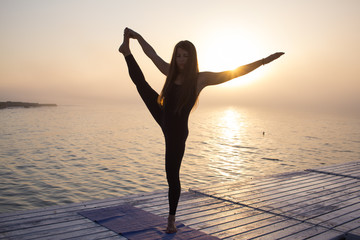 Young fit woman in black sportswear training yoga during the sunrise