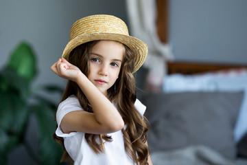 Portrait of a beautiful little girl in a straw hat studio