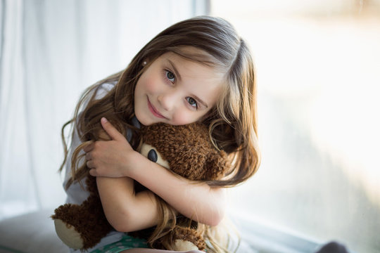 Portrait of a beautiful girl with a brown toy bear