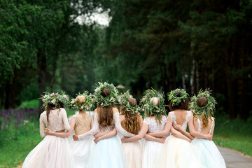 Wedding. The bride in a white dress standing and embracing bridesmaids