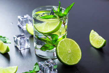 Mojito cocktail with lime, ice cubes and mint in highball glass on a black background Copy space
