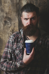 Frown bearded hipster posing with blue plastic cup