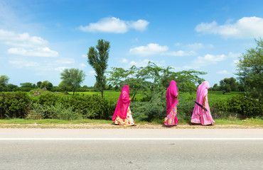 Women Walking On Road By Trees Against Sky