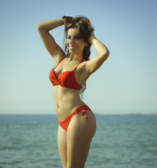 Beautiful brunette woman with red bathing suit on the beach in spain