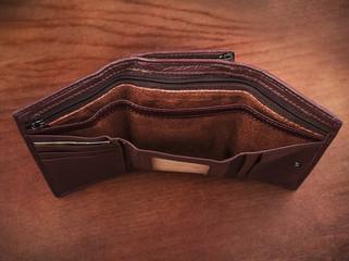 Empty purse on a wooden background; Open women's wallets