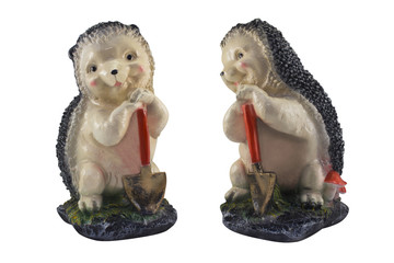 Hedgehog with shovel photo. Isolated nice cheerful ceramic hedgehog holding a shovel standing on meadow with mushrooms statuette.