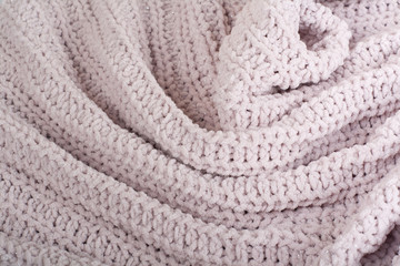 Sweater or scarf fabric texture large knitting. Knitted jersey background with a relief pattern. Wool hand- machine, handmade.